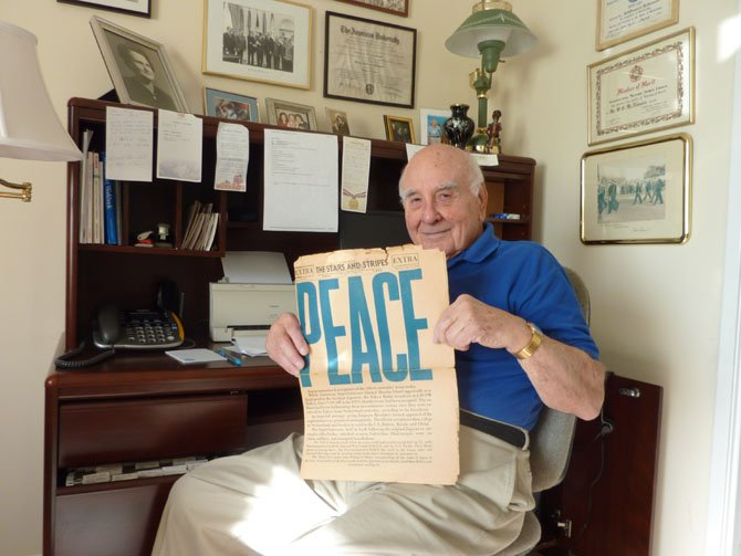 Bill McNamara holds a copy of the Stars and Stripes newspaper dated Aug. 14, 1945.