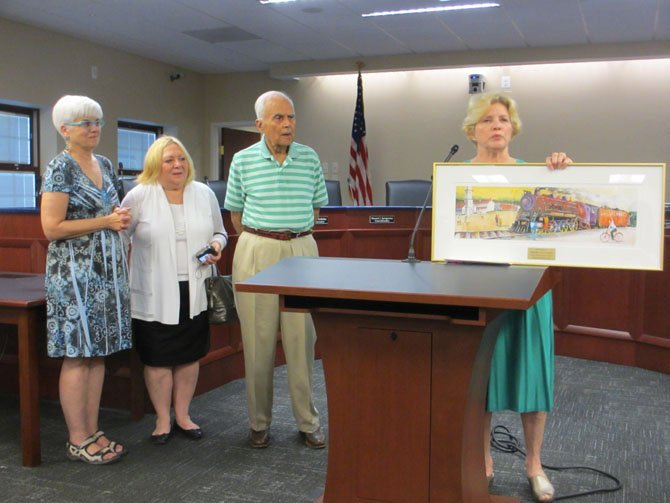 Mary Ellen Larkins, Lu Cousins, Harris Miller and Grace Rooney of the Vienna Arts Society present to the Town of Vienna a print of Miller's painting, in memory of late mayor M. Jane Seeman.