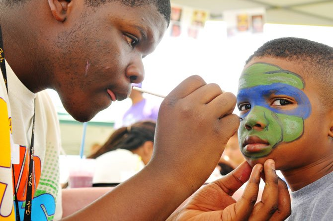 Amarri Parker adds the finishing touches to Bernard Johnson Jr.'s Ninja Turtle face mask.