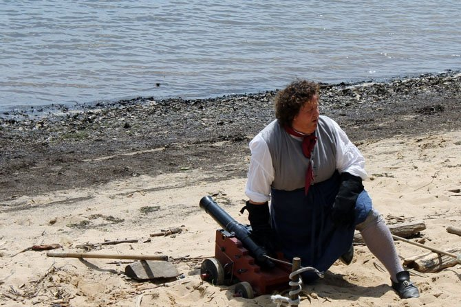 A pirate reenactor prepares to light the cannon to protect the beach from oncoming pirates at Pohick Bay Park for the annual Pirates' Day Celebration on June 7 in Lorton.