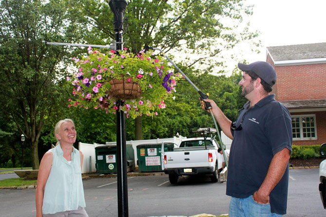 Joanne Shumpert, owner of Landscape Design Associates, chose the petunias that George Benza, owner of SGB Land Management, maintains during the early hours.