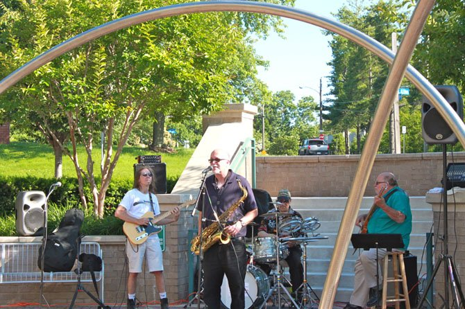 Scott Ramminger & the Crawstickers jam near the public art at the Palladium Civic Place Green Saturday.