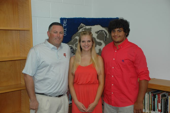 Sean Casey, father of Jackson Casey, presents scholarship awards to Clare Spitnale and Darien Pickett.