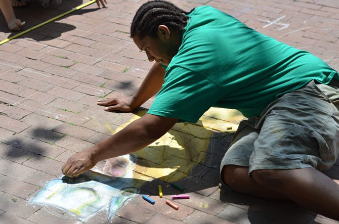 Belmin Rivera, a 2011 graduate of Reston South Lakes high school works on  his chalk mural on Saturday at Lake Anne Plaza for the June chalk festival.