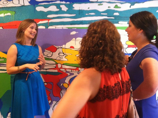 Resident artist Rachel Kerwin discusses her mural, Coloring Outside the Lines, with visitors on Thursday.