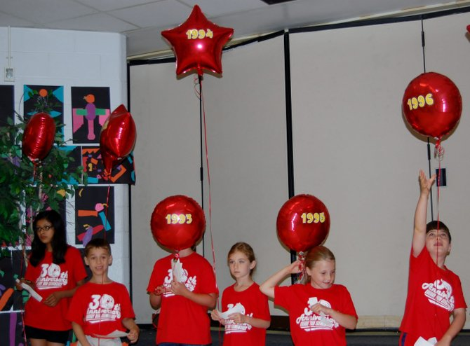 Thirty students were given balloons with a year on it and read a fact corresponding to that year at Cherry Run Elementary School's 30th anniversary celebration.