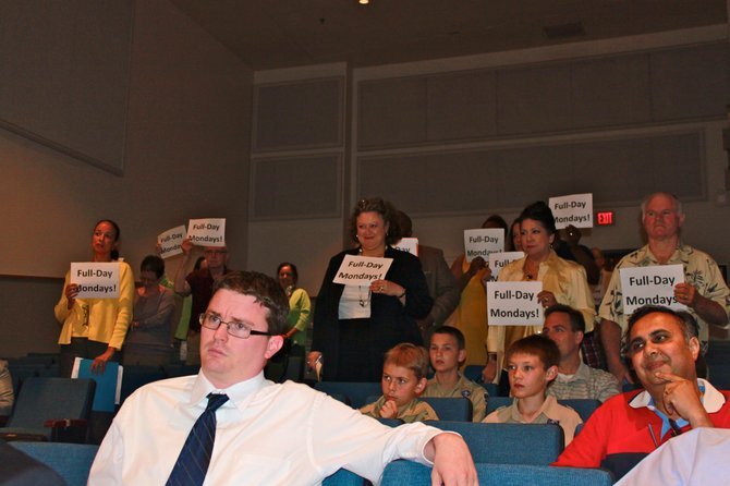 Audience members at the School Board meeting show their support for full-day Mondays.