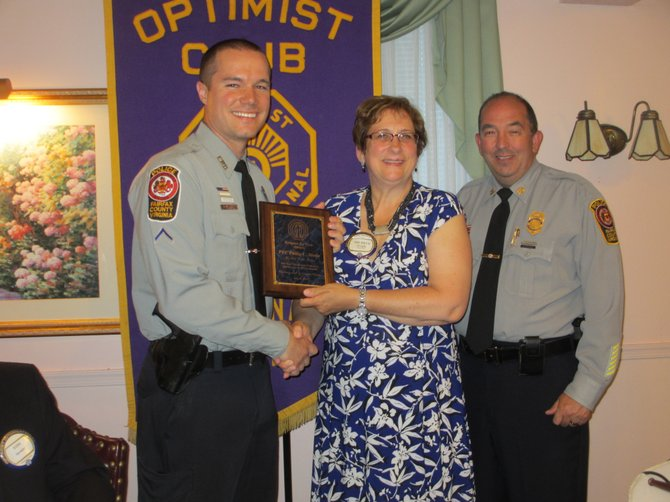 "Fairfax County police officer PFC Philip C. Stone [left] accepts the ""Charles A. Robinson Jr. Respect for the Law"" award from Vienna Optimists' vice president Michele Wright. Captain John Naylor, Commander of the Fair Oaks District Station, introduced Stone."
