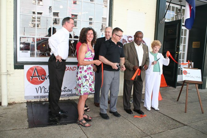 Mayor Bill Euille and Councilwoman Del Pepper joined shop owner Pierre Paret and invited guests to cut the ceremonial grand opening ribbon.