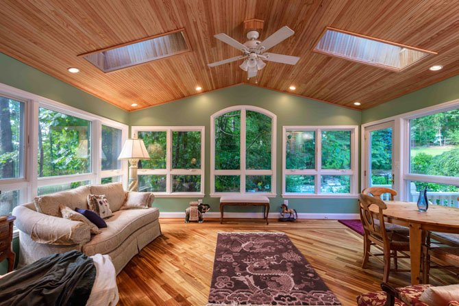 The sun porch solution emphasizes views. Windows are insulated and wind-resistant. To meet code requirements for the larger window panels the owners were seeking, remodeler David Foster developed a steel bracing frame which is concealed behind walls.