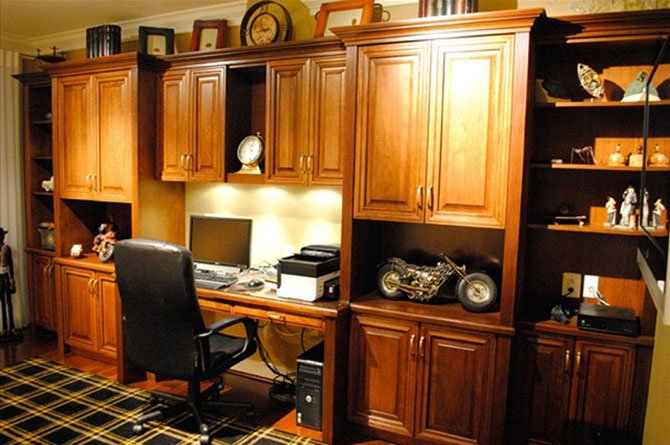 Bart Goldstein of Bart Goldstein Interior Design combined a mixture of hidden and open cabinetry with comfortable seating to create this home office.