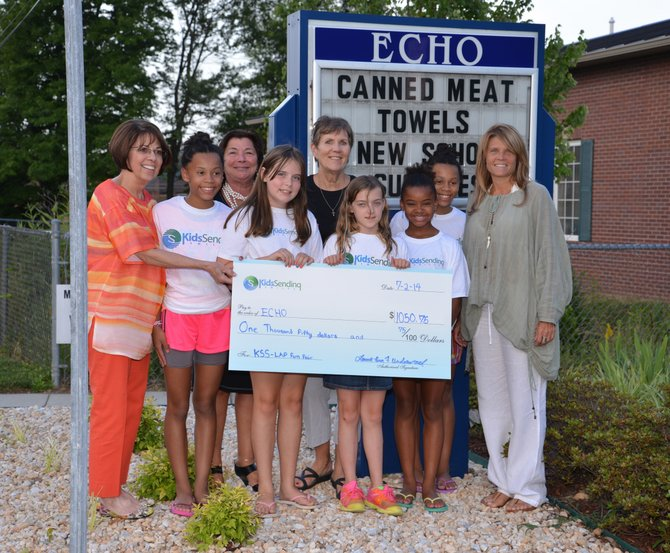 The girls from Kids Sending Smiles present the funds they raised at a Family Fun Fair for Ecumenical Community Helping Others (ECHO) at ECHO's facility in Springfield. Pictured, from left, are ECHO Director Meg Brantley, Alliyah Beard, The Little Acorn Patch Administrative Dir. Carmella Alves, Samantha Wenger, ECHO Clothing Co-Chair Kathy Marchetti, Samantha Underwood, Tatiana Joseph, Adaya Beard, and The Little Acorn Patch Owner/Director Andrea Siciliano.