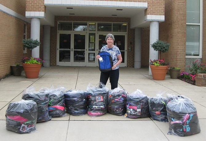 Pam Fruit, the backpack coordinator for Centreville Baptist Church, poses with some of the more than 150 backpacks her church provided last year via WFCM for students in need at London Towne Elementary. The photo was taken on delivery day.