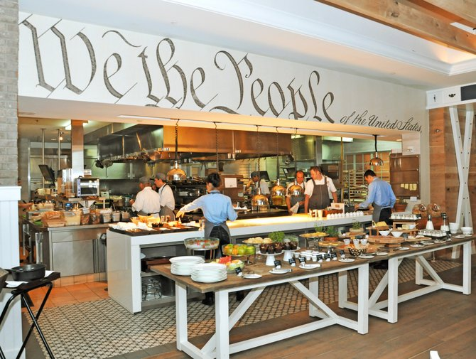 The main dining hall includes a direct view of the bright, open kitchen where diners can view the chefs at work. Framing the kitchen is a bold excerpt from the U.S. Constitution.
