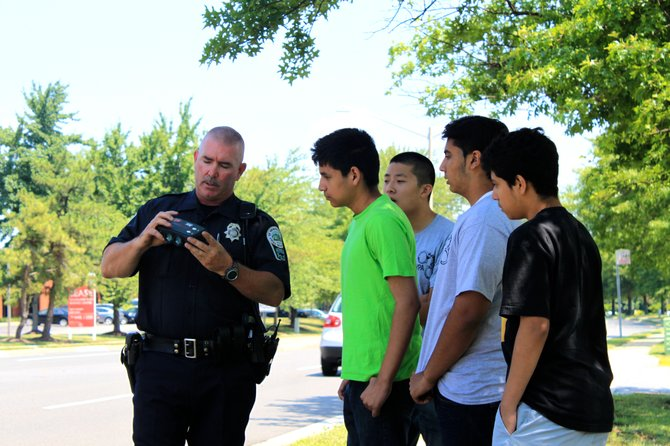 Herndon traffic motor officer Eddie Stapleton shows teens how to use a lidar during the Herndon Police Youth Academy on Friday.