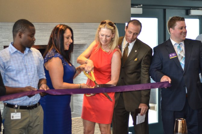 Katherine Cordero, property manager for Metropolitan at Reston cuts the ribbon with Reston Chamber of Commerce Board Chair Karen Cleveland on the rooftop of the Metropolitan at Reston.
