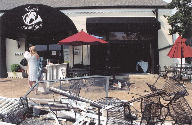Guests were seated in what was once a fenced-­in patio at Hunter's Bar and Grill prior to a driver failing to stop her car, jumping the curb, and entering the Polo Room. Two guests were injured. One of the tables not crushed can be seen inside the Polo Room.