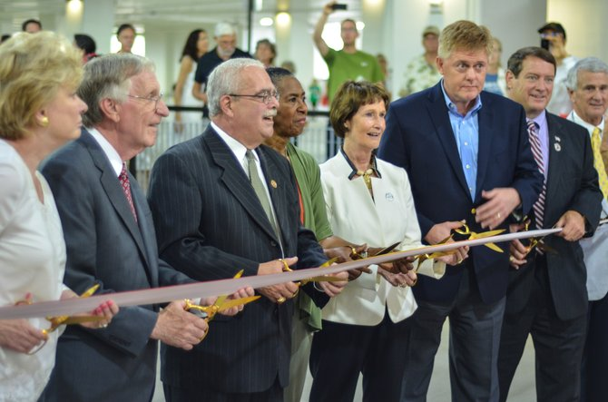 Virginia state senator Janet Howell, Del. Ken Plum, US Congressman Gerald Connolly, Supervisor Cathy Hudgins, Chairman for the Fairfax County Board of Supervisors Sharon Bulova, Supervisor John Cook, Supervisor Pat Herrity, and Del. Tom Rust prepare for the ceremonial ribbon cutting at the Wiehle-Reston East garage held on July 19 in Reston.