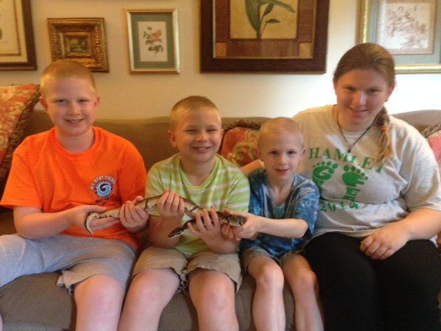 From left -- John, Robbie, Andrew, and Ashley King hold their pet Python Zed.