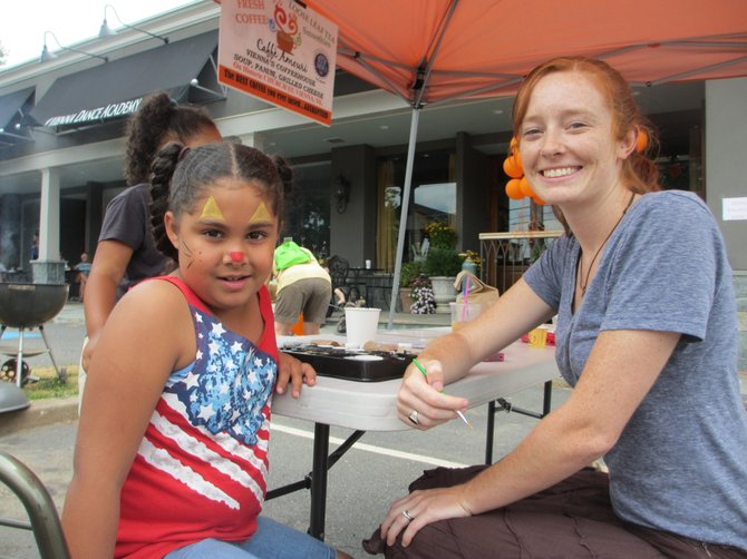 Six-year-old Nina Mendez has her face painted by Caffe Amouri volunteer Kristen Amouri. Nina's mom said the family came to support the Lamb Center.