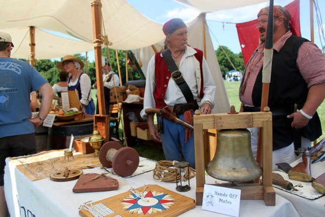 Pirate re-enactors Alpheus Chewning and Jack Morgan show off reproductions of 17th and 18th century compasses and lamps at Pirate Fest.