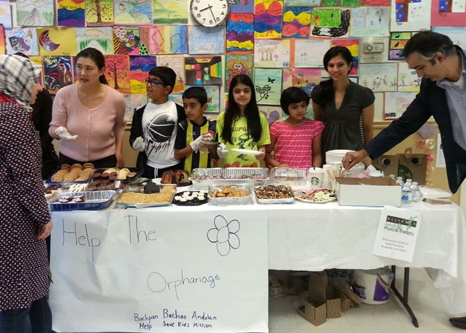 Wearing yellow shirts, Kushaan and Medhnaa Saran work at the bake sale with their friends.
