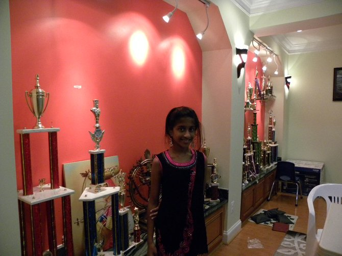 Aasa Dommalapati has won many chess tournaments. Her father, Anand, displays both of his children's trophies in the basement.