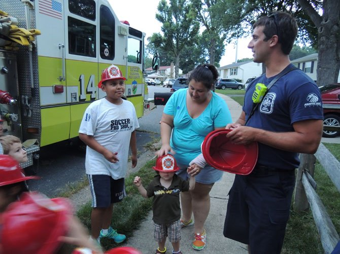 Firefighter Happ Radam of Engine 14 in Burke talks with Jack Sejas, 11, about fire safety. Radam handed out hats to all the kids before they climbed into the engine to discover what was inside.