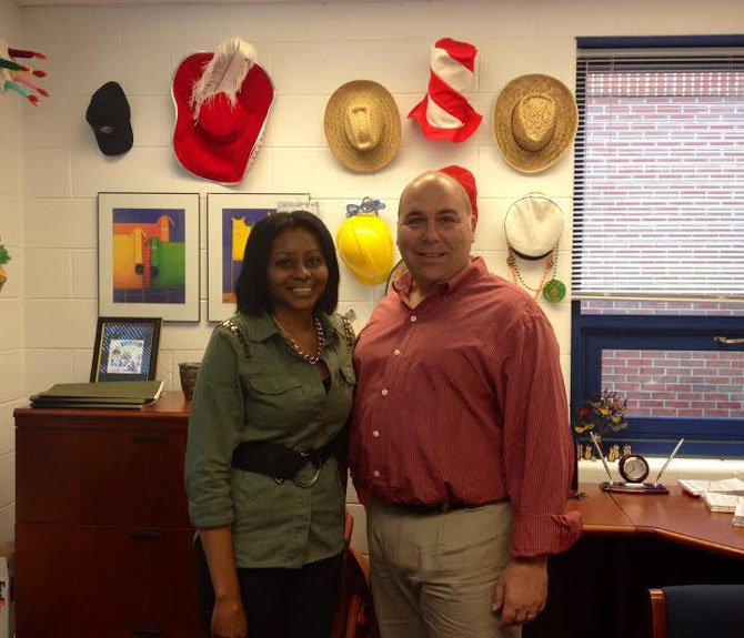 Principal Don Hutzel and Assistant Principal Sharon Jones of Churchill Road ES in front of a display of hats that reflect the school's spirit days.