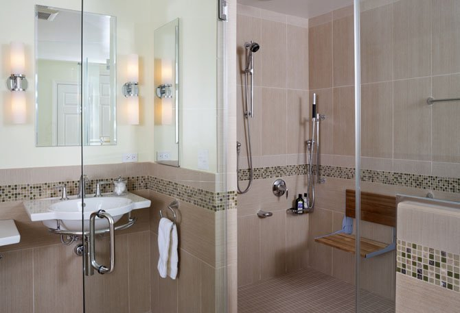 When remodeling this bathroom, Glickman Design Build added a bench to this shower. Such features can help seniors to downsize and live alone safely.