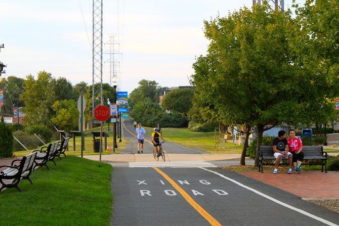 A cyclist and pedestrian cross a street on the Washington and Old Dominion Trail.