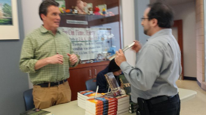 Author Louis Bayard (left) signs a copy of a book for a fan.