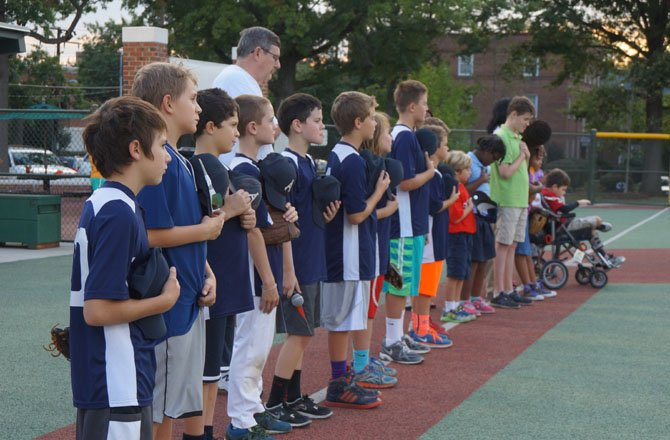 Players and volunteers  listen to the National Anthem Sept. 19 prior to the opening game of the 2014 Miracle League fall season at the Nannie J. Lee Center.