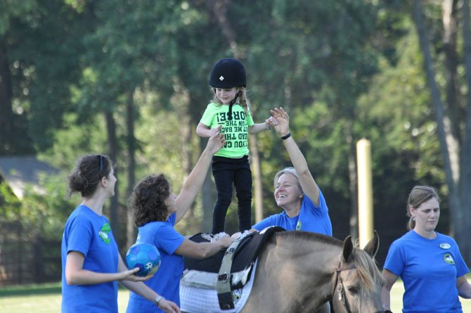 (From left) NVTRP volunteers Katie Breese, Debbie Heitmann, Patti Towsley and Sarah Maceyak supervise Alyssa Peterson (center) during a therapeutic riding demonstration.