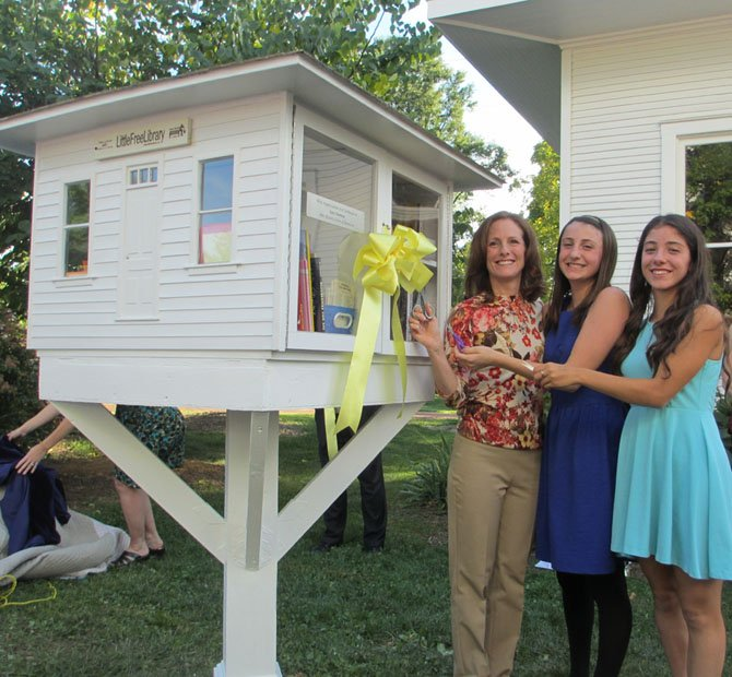 Vienna's late Mayor M. Jane Seeman's daughter, Linda Colbert, now a Town Council member, and granddaughters, Hannah and Heather Colbert, cut the yellow ribbon tied around the mini-library perched birdhouse-height. Colbert reflected on her mother's love of reading in her remarks.