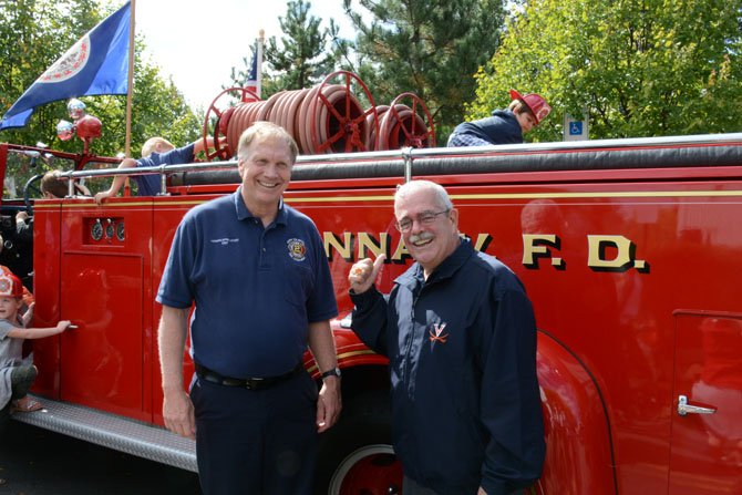 Howard Springsteen (left) of the Vienna Town Council and U.S. Rep. Gerry Connolly (right) hand out plastic fire helmets in front of a 1946 fire truck at the Oct. 4 Oktoberfest in Vienna.