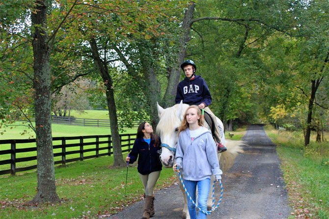 From left, Caroline McGranahan and Christina Saunders lead Richard Tucker and horse Nyles during a trail ride at Lift Me Up! riding program.