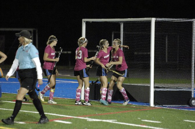 Members of the Fairfax field hockey team celebrate with sophomore Emily Deivert, right, after she scored one of her two goals against Madison on Oct. 9.