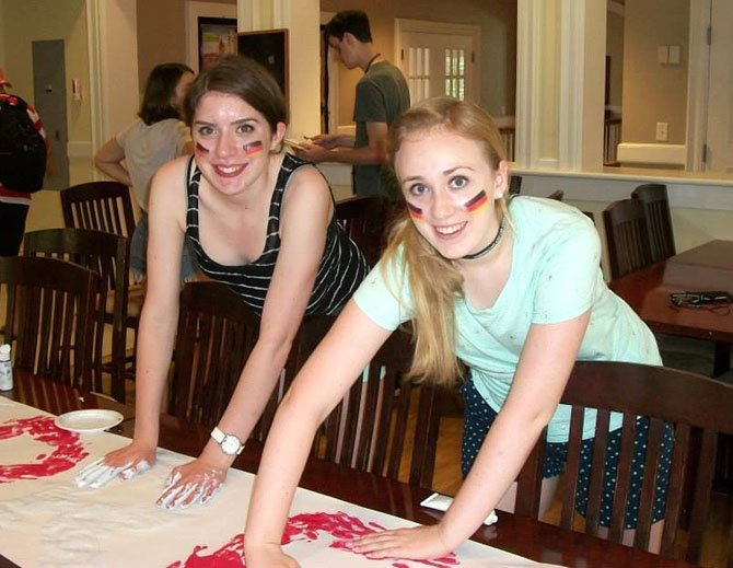 Kate Meyer (left) and friend Hannah work together on a banner for Austria in their arts-and-crafts class at the academy.