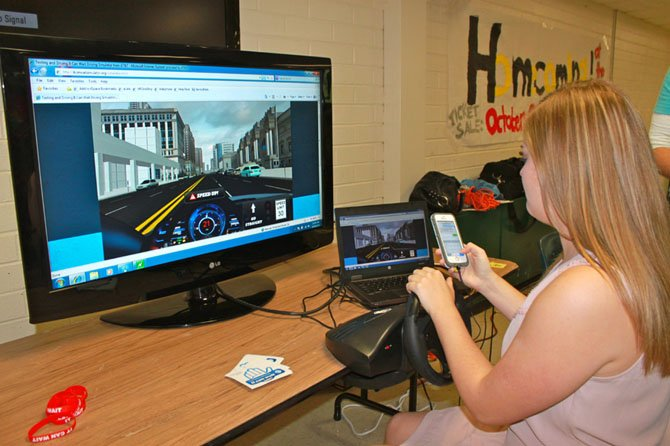 Langley High School senior Hanna Hunt behind the wheel of a texting and driving simulator on Oct. 16. Students could sign a pledge to never text again as a part of the school year's theme of road safety.