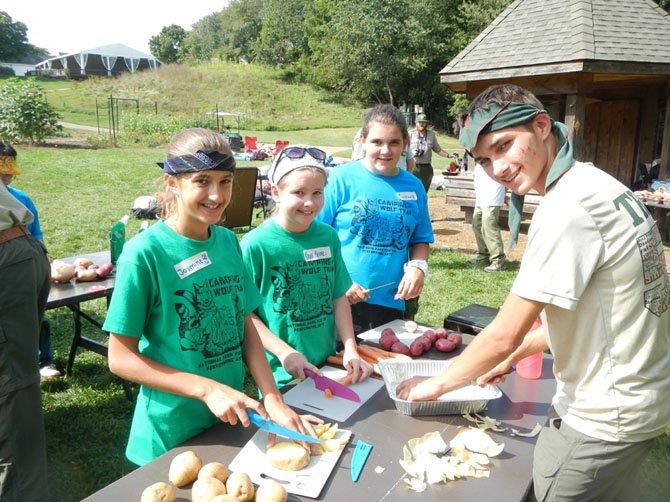 Jasmine Bhatia, Nora Reinke, Caroline Bennett and Nick Tagliatelle (scout) prepare a meal.