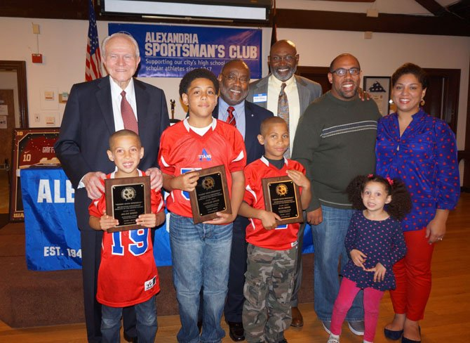 Greer brothers Julian, 7, Charles, 13, and Miles, 9, front, are joined by their parents Jeremie and Elena, at right, and sister Leila, 3, after being presented the Alexandria Sportsman's Club  Athlete of the Month Awards Oct. 21 at the Old Dominion Boat Club. With them in back are ASC president Allan Kaupinen, Mayor Bill Euille and Redskins great Mike Nelms.