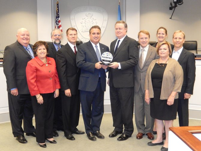 The award presentation at the Oct. 14 Fairfax City Council meeting. (From left) are Doug Church, chairman, Central Fairfax Chamber of Commerce; Council members Ellie Schmidt, Michael DeMarco and Jeff Greenfield; Mayor Scott Silverthorne; John Sullivan, legislative counsel, Google; Council members David Meyer, Nancy Loftus and Janice Miller (in front) and John Sabo, chairman, Fairfax City Economic Development Authority.