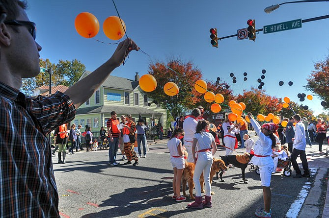 Volunteers add a long string of seasonally colored balloons to the start line of the Halloween parade.
