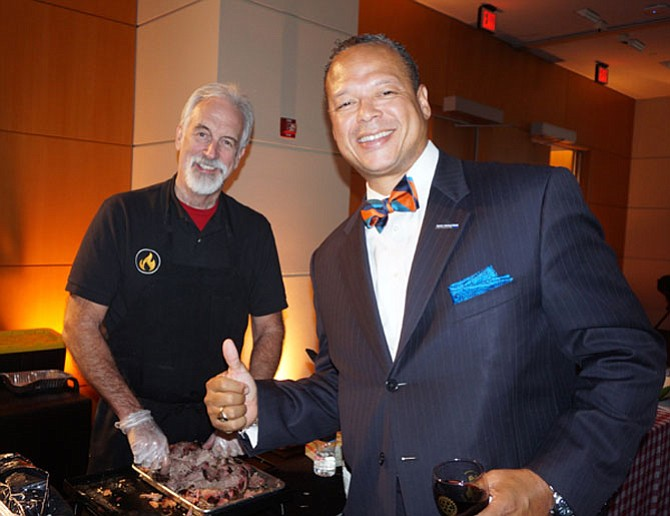 """Mango"" Mike Anderson, left, dishes out Sweet Fire Donna's BBQ to Burke and Herbert vice president Walter Clarke at the Rotary Club of Alexandria's Taste For Giving fundraiser Oct. 24 at the USPTO."