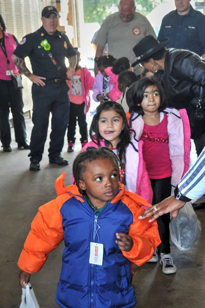 Students dressed in their new winter jackets and carrying new athletic shoes prepare to board the bus back to the Gum Springs Head Start.