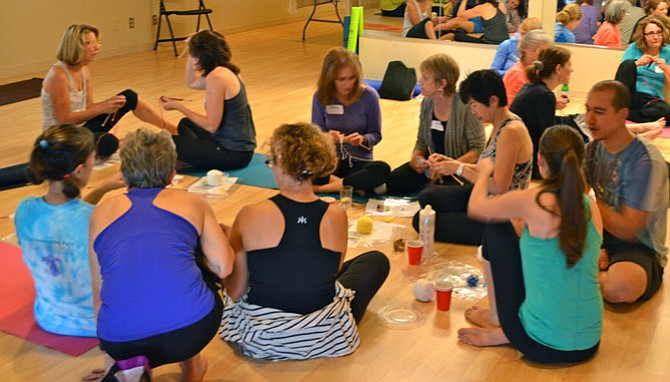Participants at a local fundraiser for Project Knitwell learn to knit after taking a yoga class at Pengu Studio in McLean.