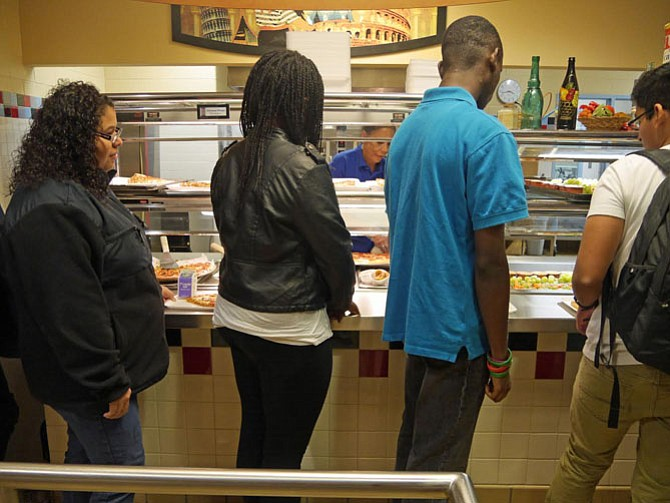 "Students move through Napper's pizza line quickly to choose pepperoni (the big favorite) pizza, cheese or the ""speciality of the day"" which is barbecued chicken on this Homecoming Friday."