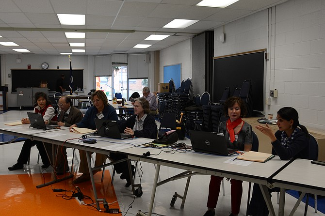 Election officials at West Springfield High School wait to process voters. (From left) Chea Belfort of Burke, Pradeep Chaturvedi of Springfield, Jeanette Hantke of West Springfield, Vivina McVay of Burke, Chris Bolognese of Springfield and Nour Nourey of Alexandria.