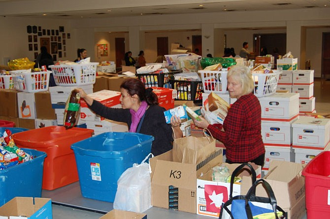 Volunteers help to sort food at food drive. Five-hundred twenty-five households in southeastern Fairfax County were served a Thanksgiving food basket from Lorton Community Action Center, thanks to donations from the community and volunteers to organize the packing.